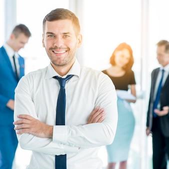 Heureux homme d'affaires pliant ses bras avec ses collègues en arrière-plan