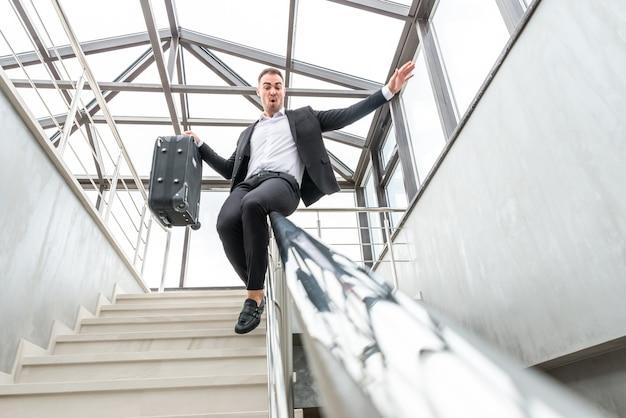Heureux homme d'affaires portant un costume formel glissant sur les escaliers garde-corps dans un immeuble moderne. concept de hâte et de liberté