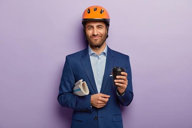 Heureux homme d'affaires posant en costume élégant et casque rouge au bureau
