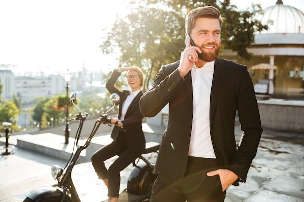 Heureux l'homme d'affaires posant à l'extérieur en parlant par téléphone