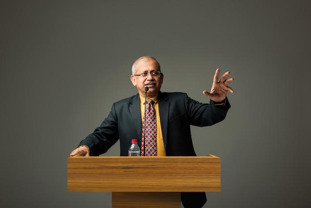 Heureux homme d'affaires senior asiatique indien heureux parlant avec micro au podium au bureau ou à l'auditorium présentant quelque chose