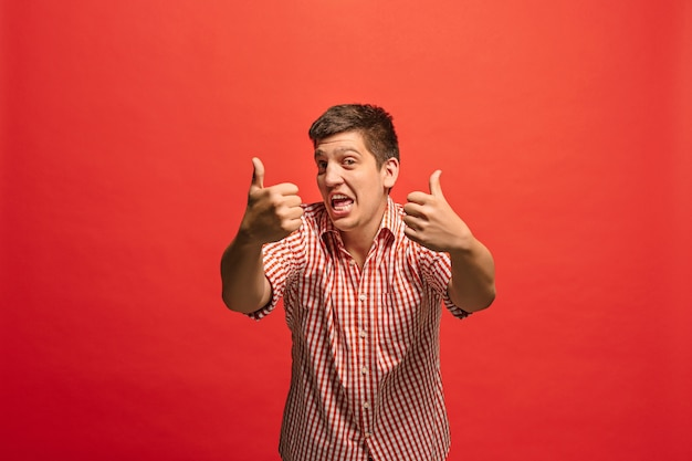 Heureux homme d'affaires, signe ok, souriant, isolé sur fond de studio rouge à la mode. beau portrait mâle demi-longueur.