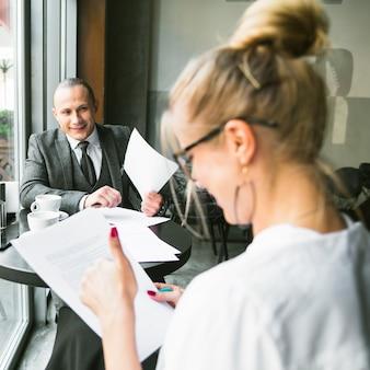 Heureux homme d'affaires avec son partenaire travaillant sur un document dans un café