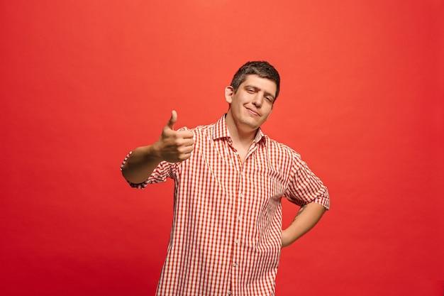 Heureux homme d'affaires souriant, isolé sur le mur de studio rouge à la mode