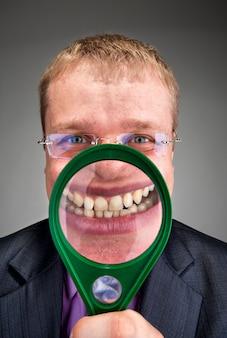 Heureux homme d'affaires vous souriant à travers une loupe