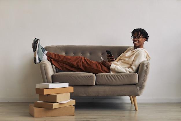 Heureux homme africain allongé sur un canapé avec des piles de colis sur le sol et souriant à la caméra tout en achetant des achats en ligne sur le téléphone