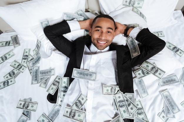 Heureux homme africain en costume allongé sur le lit dans la chambre d'hôtel avec de l'argent qui tombe et regardant la caméra