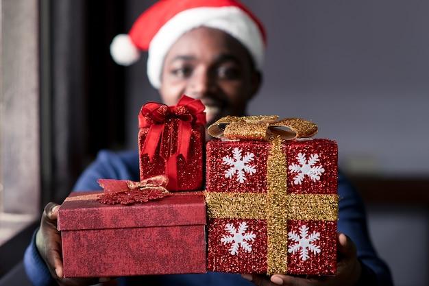 Heureux homme africain donnant un cadeau de noël.