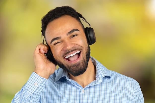 Heureux homme africain souriant, écoutant de la musique au casque. fond blanc