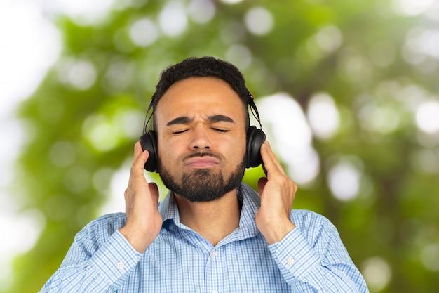 Heureux homme africain souriant, écoutant de la musique dans les écouteurs