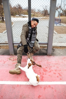 Heureux homme africain souriant et jouant avec un chien à l'extérieur