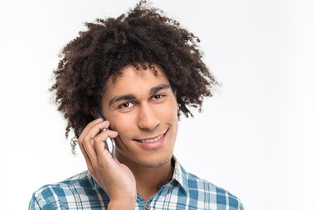 Heureux homme afro-américain aux cheveux bouclés parlant au téléphone et regardant isolé sur un mur blanc
