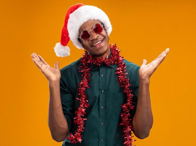 Heureux homme afro-américain en bonnet de noel avec guirlande portant des lunettes souriant avec les bras levés debout sur le mur orange