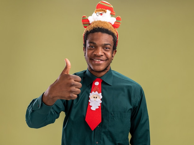 Heureux homme afro-américain avec drôle de santa jante et cravate rouge regardant la caméra montrant les pouces vers le haut souriant debout sur fond vert