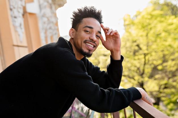 Heureux homme afro-américain portant pull noir posant sur la terrasse extérieure.