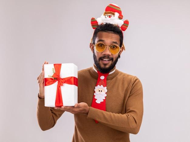 Heureux homme afro-américain en pull marron et santa rim sur la tête avec une cravate rouge drôle tenant un cadeau regardant la caméra avec le sourire sur le visage debout sur fond blanc
