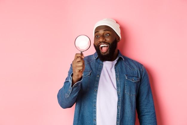 Heureux homme afro-américain regardant à travers une loupe, souriant étonné, debout sur fond rose. espace de copie