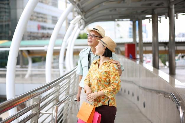 Heureux homme âgé et femme marchant dans la rue dans une journée d'été. couple de personnes âgées détendu avec des chapeaux pour faire du shopping.