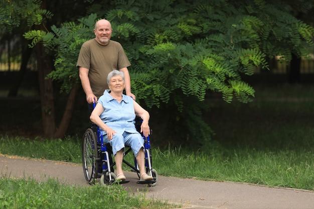Heureux homme âgé marchant avec une femme âgée handicapée assise en fauteuil roulant à l'extérieur
