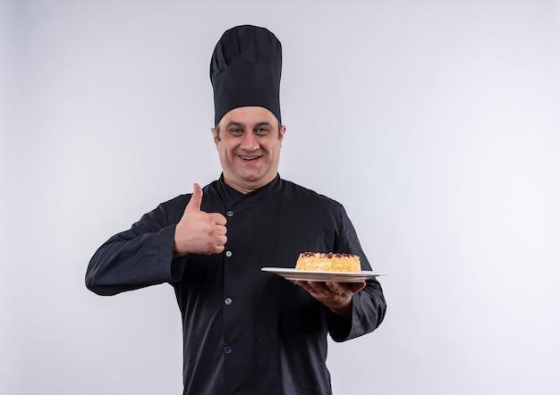 Heureux homme d'âge moyen cuisinier en uniforme de chef holding cake sur plaque son pouce vers le haut sur un mur blanc isolé avec copie espace