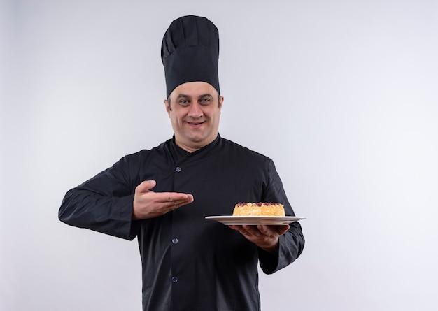 Heureux homme d'âge moyen cuisinier en uniforme de chef montrant un gâteau sur une assiette à la main sur un mur blanc isolé avec copie espace