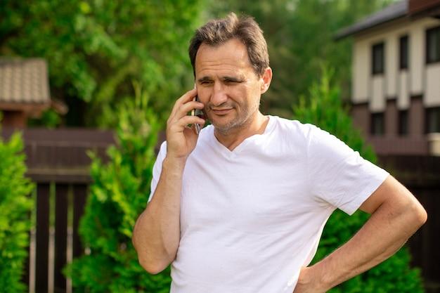 Heureux homme d'âge moyen dans des vêtements décontractés faisant appel téléphonique à l'extérieur, bel homme d'affaires parlant au téléphone mobile avec la famille, les collègues de travail. communication, personnes, concept numérique