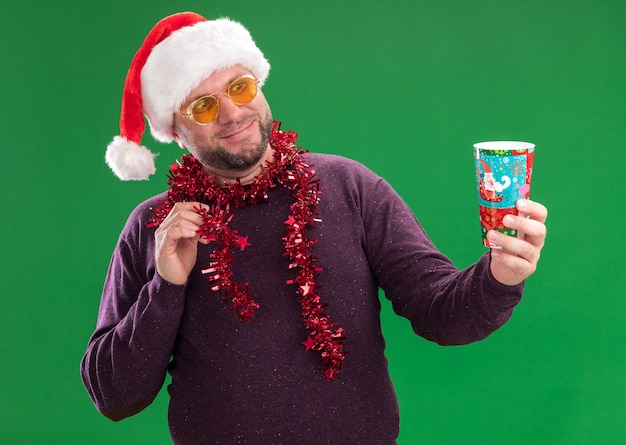 Heureux homme d'âge moyen portant bonnet de noel et guirlande de guirlandes autour du cou avec des lunettes qui s'étend de la tasse de noël en plastique en le regardant toucher guirlande de guirlandes isolé sur mur vert