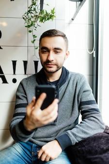 Heureux homme à l'aide de smartphone au café moderne
