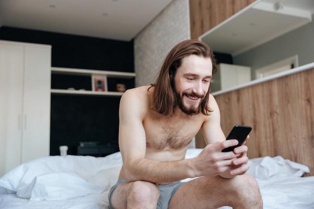 Heureux homme à l'aide de téléphone portable assis sur le lit dans la chambre