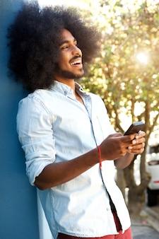 Heureux homme appuyé contre le mur avec un téléphone mobile
