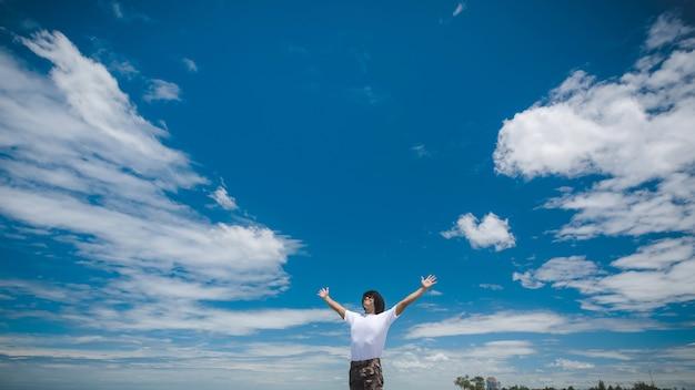Heureux homme asiatique debout sur la plage de rochers avec un ciel bleu