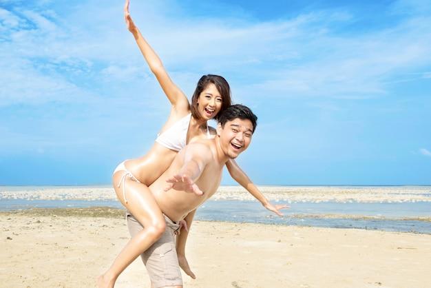 Heureux homme asiatique portant une fille sur le dos sur la plage