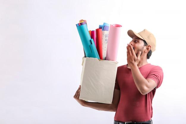 Heureux homme asiatique en t-shirt et casquette tenant une boîte de papier de couleur isolée sur fond blanc, concept de service de livraison