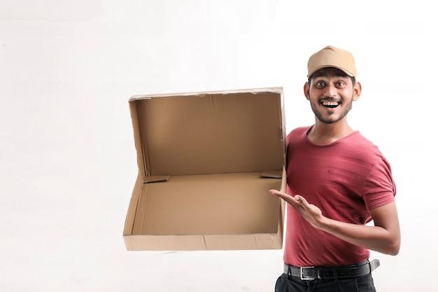 Heureux homme asiatique en t-shirt et casquette tenant une boîte vide isolée sur fond blanc, concept de service de livraison
