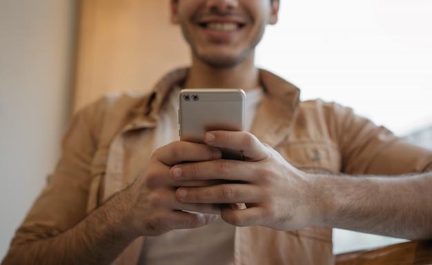 Heureux homme asiatique tenant un téléphone portable, discuter, recevoir un message texte, réserver des billets, se concentrer sur les mains