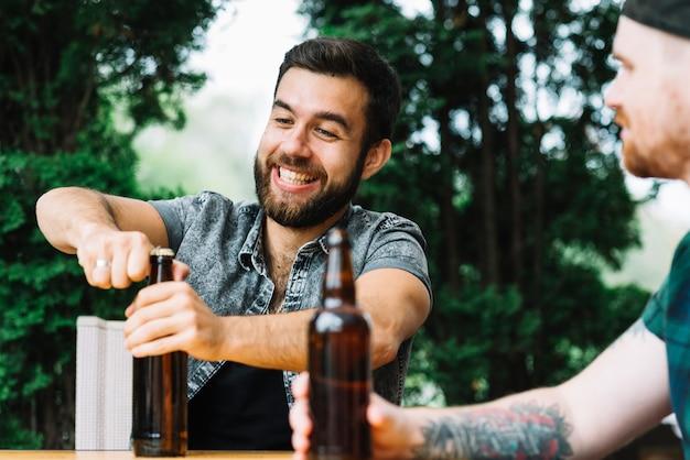 Heureux homme assis avec un ami ouvrant la bouteille de bière à l'extérieur