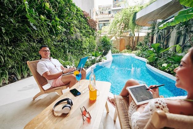 Heureux homme assis dans un fauteuil au bord de la piscine, travaillant sur un ordinateur portable et regardant sa femme dessiner un croquis de mode sur une tablette numérique