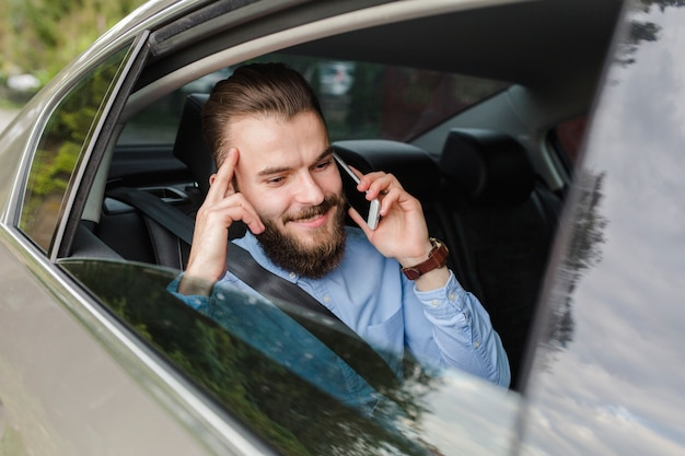Heureux homme assis à l'intérieur d'une voiture parlant sur smartphone