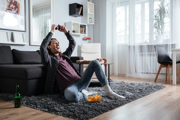 Heureux homme assis à la maison à l'intérieur jouer à des jeux avec joystick