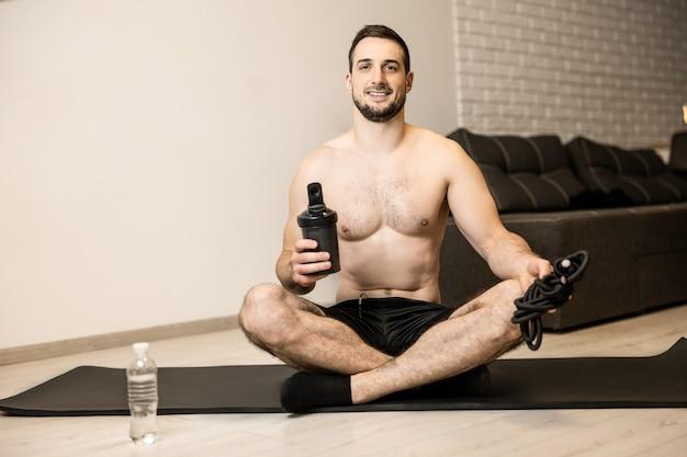 Heureux homme assis en posture de lotus, regardant la caméra, souriant et se sentant bien après la méditation. concept de mode de vie sain. prenez soin de votre santé mentale. homme faisant de l'exercice dans sa chambre moderne.