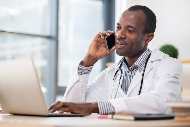 Heureux homme assis sur son lieu de travail tout en parlant par téléphone