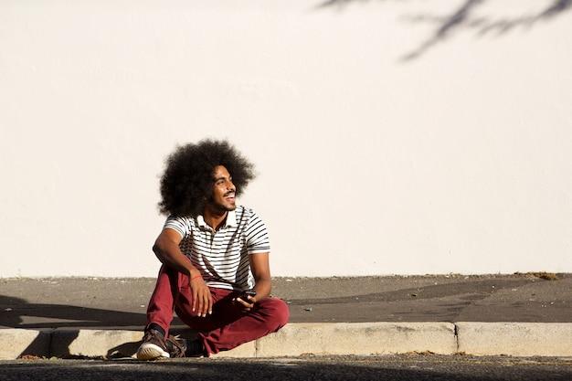 Heureux homme assis sur le trottoir à l'extérieur avec téléphone