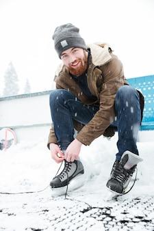 Heureux homme attachant des lacets sur des patins à glace à l'extérieur