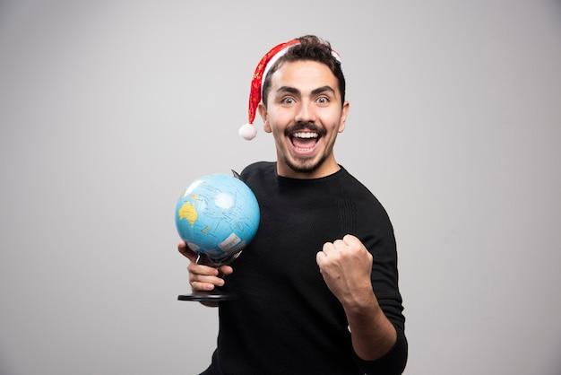 Heureux homme au chapeau du père noël tenant un globe.