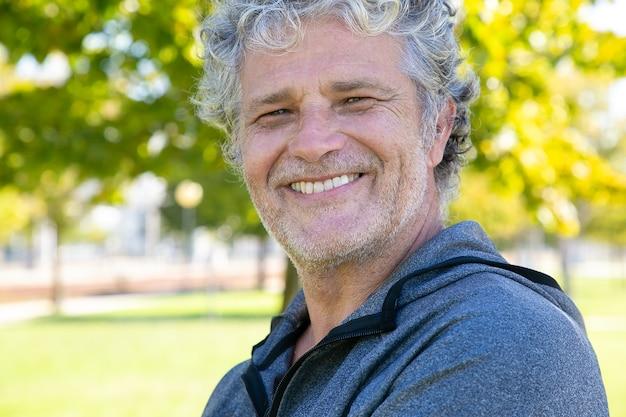 Heureux homme aux cheveux gris en tenue de sport debout à l'extérieur, un et souriant. photo en gros plan. personne sportive mature ou concept de mode de vie actif