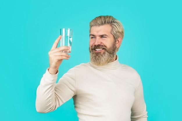 Heureux homme barbe eau potable. homme buvant dans un verre d'eau.