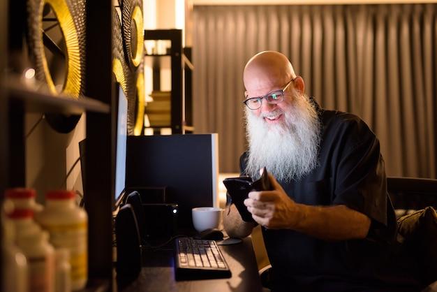Heureux homme barbu chauve mature à l'aide de téléphone tout en travaillant des heures supplémentaires à la maison tard dans la nuit