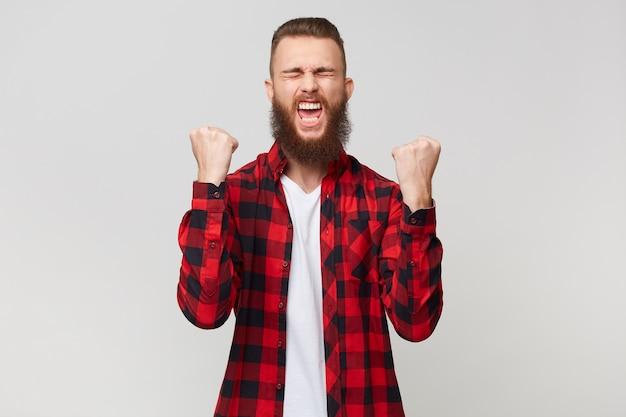 Heureux homme barbu en chemise à carreaux serrant les poings comme gagnant avec les yeux fermés de plaisir, crie au sujet de sa victoire célèbre sa victoire, isolé sur fond blanc