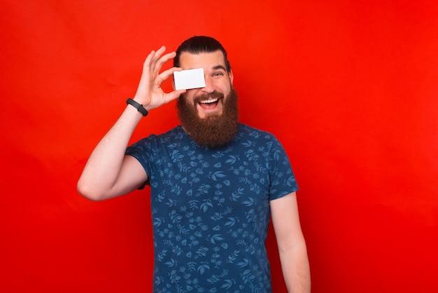 Heureux homme barbu couvre son œil avec une carte de crédit ou de contact sur fond rouge.