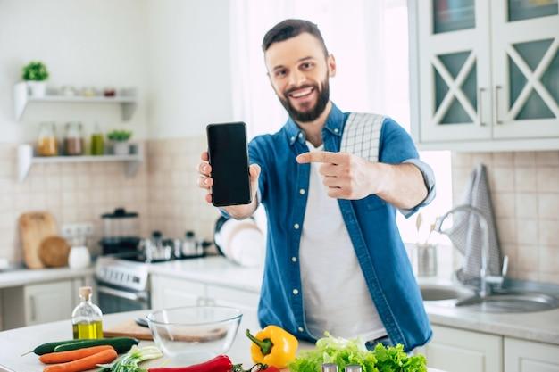 Heureux homme barbu dans la cuisine à la maison pendant qu'il prépare la salade végétalienne fraîche et saine et pointant sur le téléphone intelligent